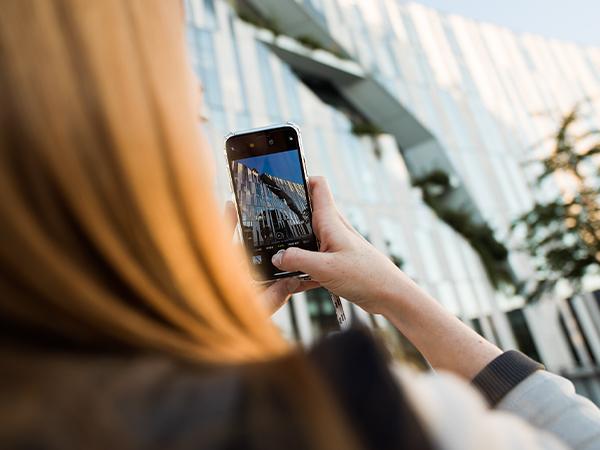 Eine junge rothaarige Frau macht mit ihrem Smartphone ein Foto von einem modernen Gebäude mit Glaswand.