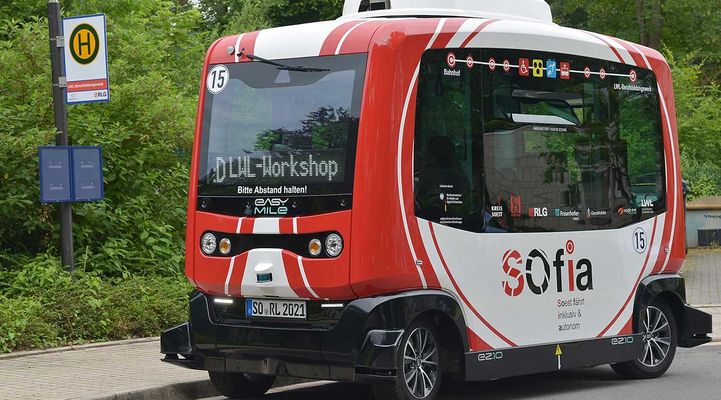 Ein kleiner rot-weißer Shuttlebus steht an einer Bushaltestelle.