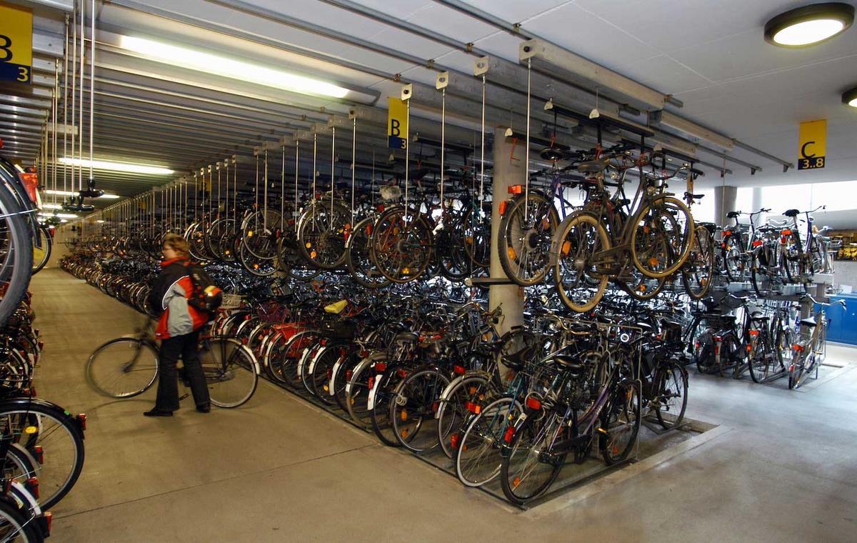 In einem Fahrradparkhaus stehen in großen Blöcken zahlreiche Fahrräder nebeneinander und hängen teilweise von der Decke.