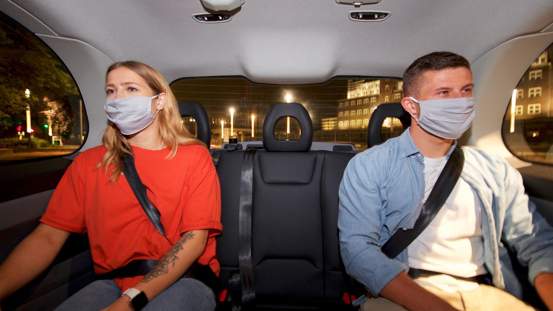 Eine junge Frau und ein junge Mann sitzen mit Mund-Nasen-Bedeckung nebeneinander in einem Auto.