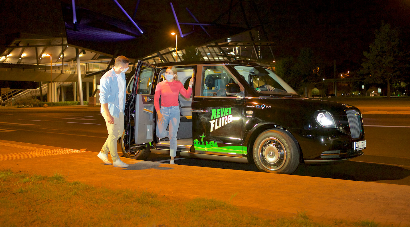 Ein junger Mann und eine junge Frau steigen nachts in ein kleines schwarzes Auto ein, auf dem der Aufkleber Revierflitzer steht.