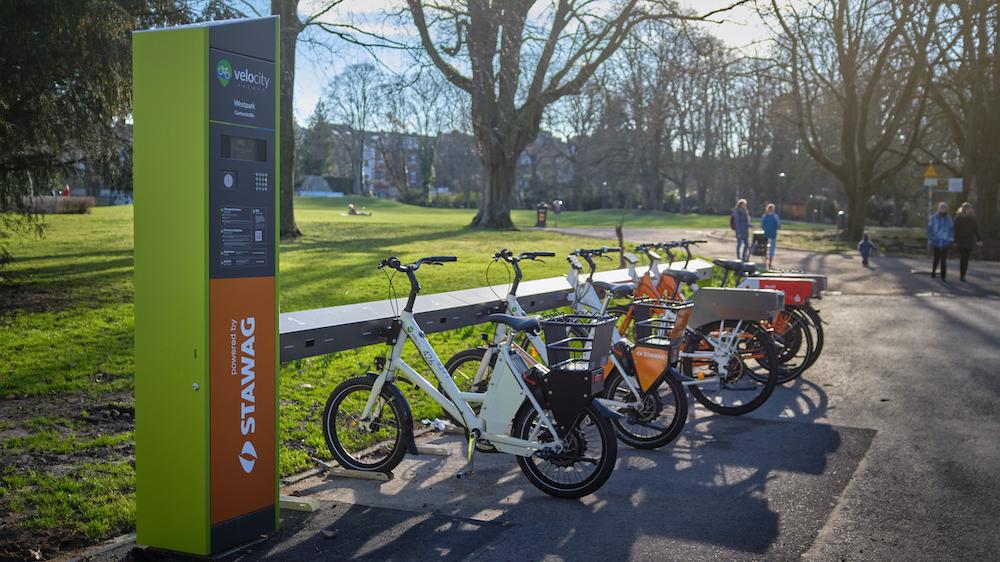 E-Bikes stehen in einer Reihe an einer Verleihstation vor einer Wiese.