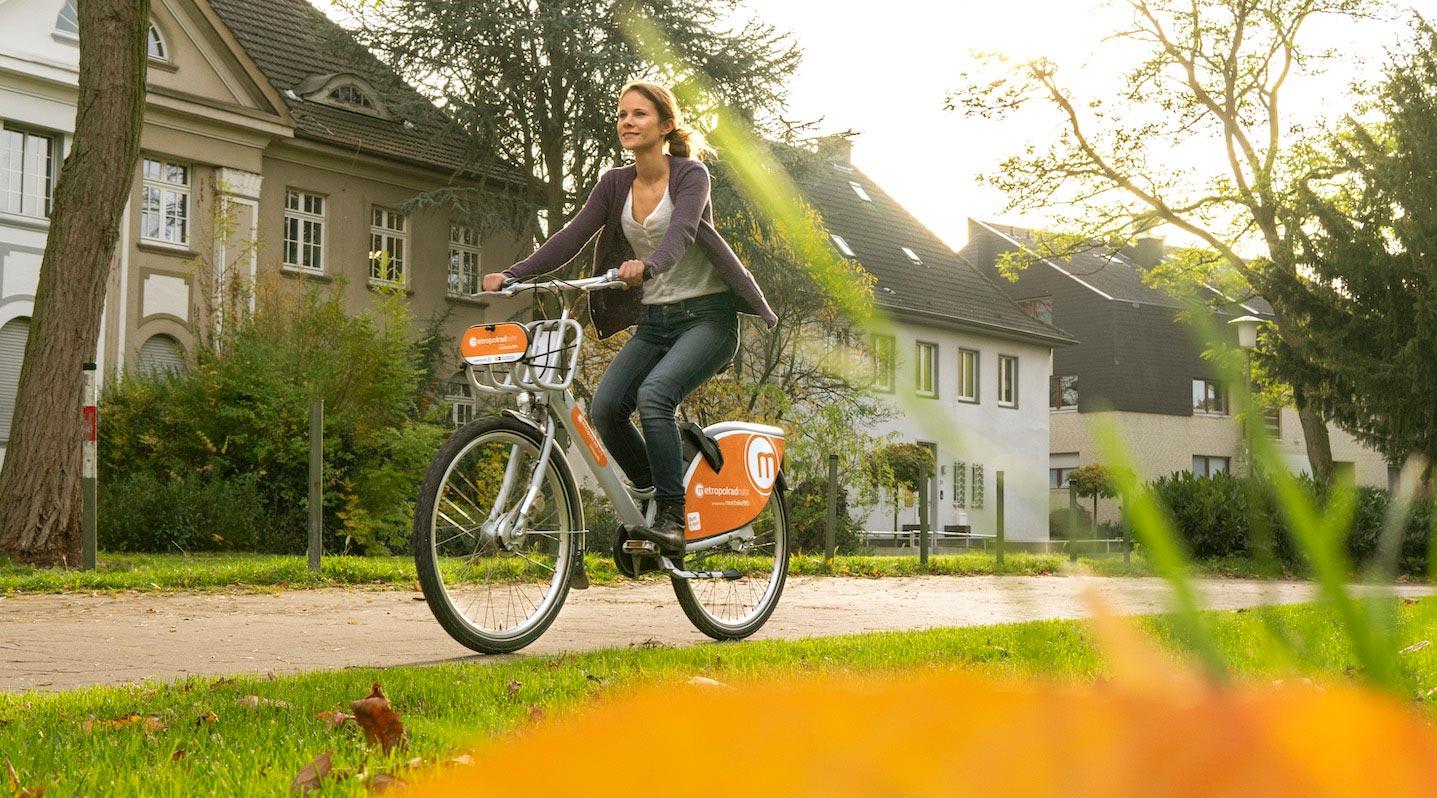 Eine Frau fährt auf einem Fahrrad über einen Naturweg neben einer Wohnsiedlung.