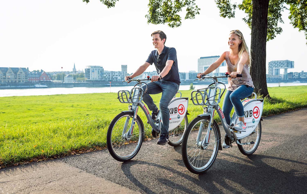 Ein Mann und eine Frau fahren auf Leihrädern über einen natürlichen Weg am Rhein in Köln entlang.