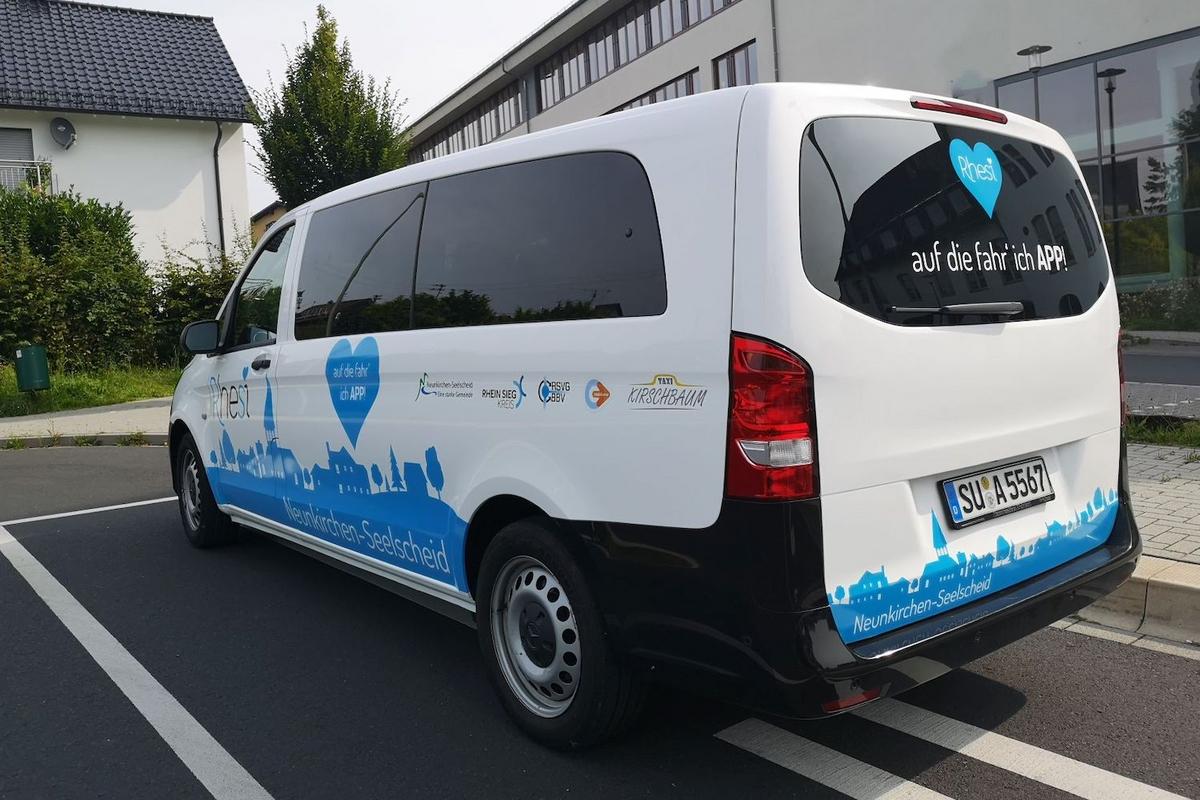 Ein weißer Kleinbus, auf dessen Seite eine blaue Silhouette von Neunkirchen-Seelscheid und der Schriftzug Rhesi geklebt wurde.