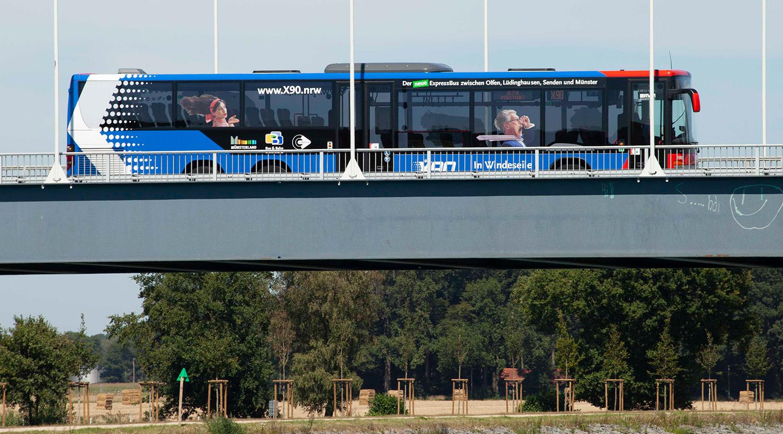 Ein blau-roter Bus fährt über eine Brücke.