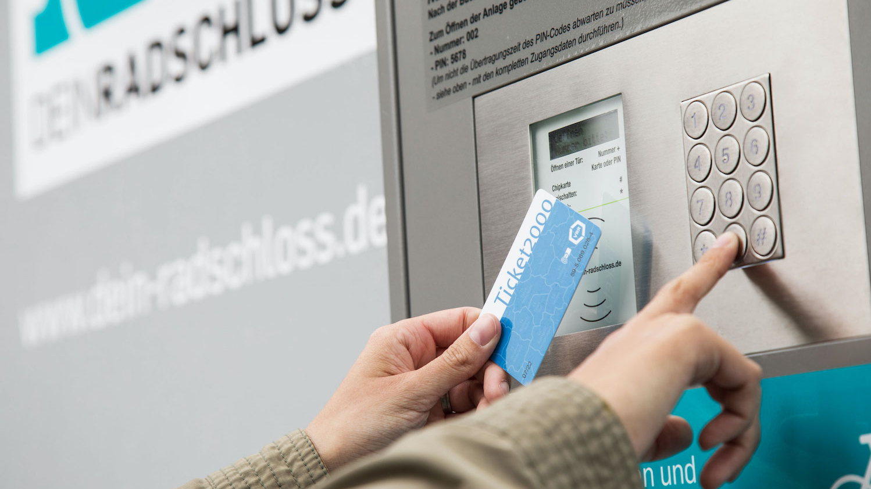 Nahaufnahme von zwei Händen vor der Tür einer Radbox. Eine Hand hält eine Fahrkarte mit elektronischem Chip vor ein Lesegerät, die andere Hand tippt einen Code auf einem Zahlenfeld ein.