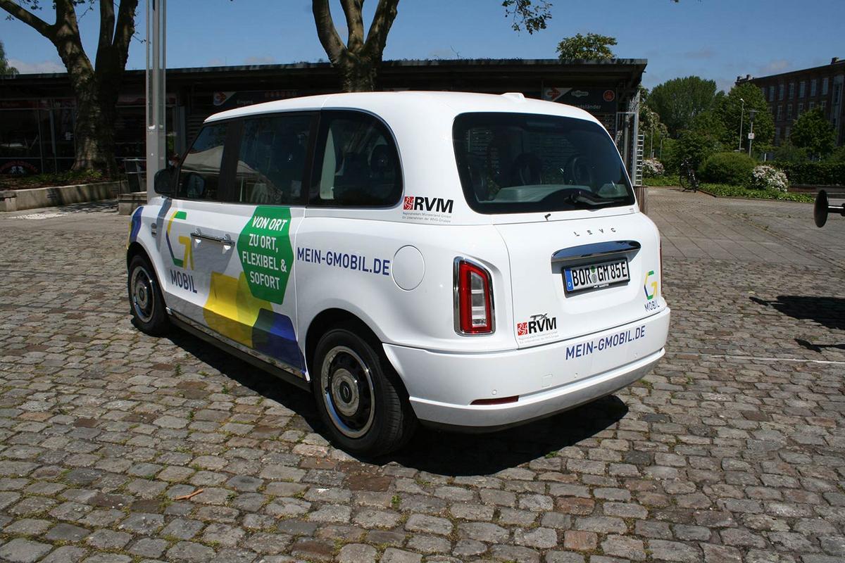 Ein kleines weißes Auto steht auf einem Kopfsteinplatz. Auf das Auto wurden gelbe und blaue Sechsecke lackiert, außerdem sind das Logo von G-Mobil und RVM abgebildet.