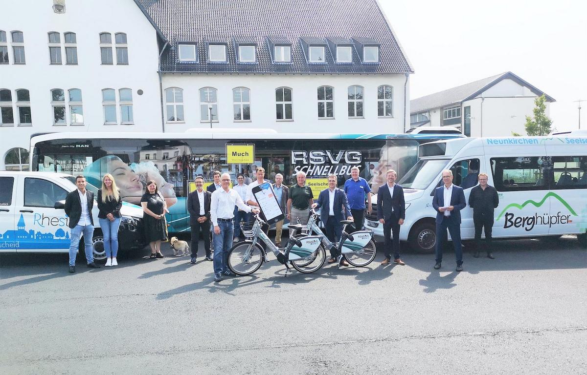 Ein Gruppenbild mit mehreren Menschen, die vor verschiedenen Kleinbussen und an Leihrädern stehen.