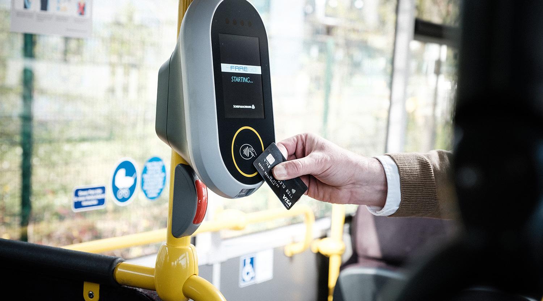 Zu sehen ist ein BONNsmart-Modul in einem Bus. jemand hält eine Chipkarte davor.