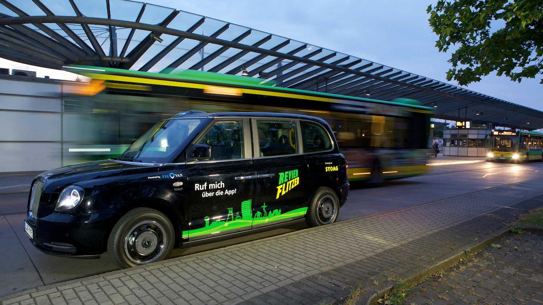 Ein kleines schwarzes Auto mit dem Aufkleber Revierflitzer steht an einer Haltestelle, im Hintergrund fahren gelb-grüne Busse.