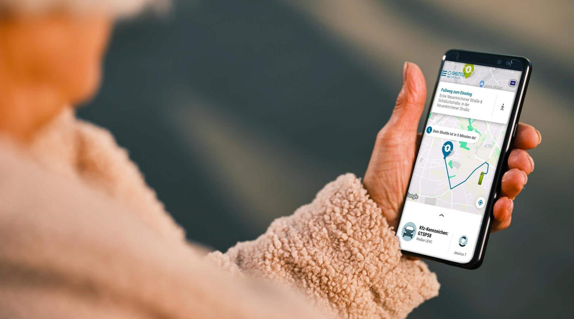 Eine Frau hält ein Smartphone in der Hand, auf dessen Bildschirm eine Route angezeigt wird.
