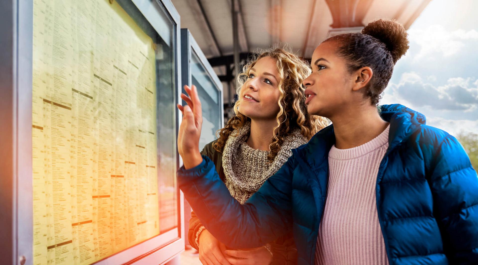Zwei junge Frauen stehen an einem Bahnsteig und betrachten den Abfahrtsplan.