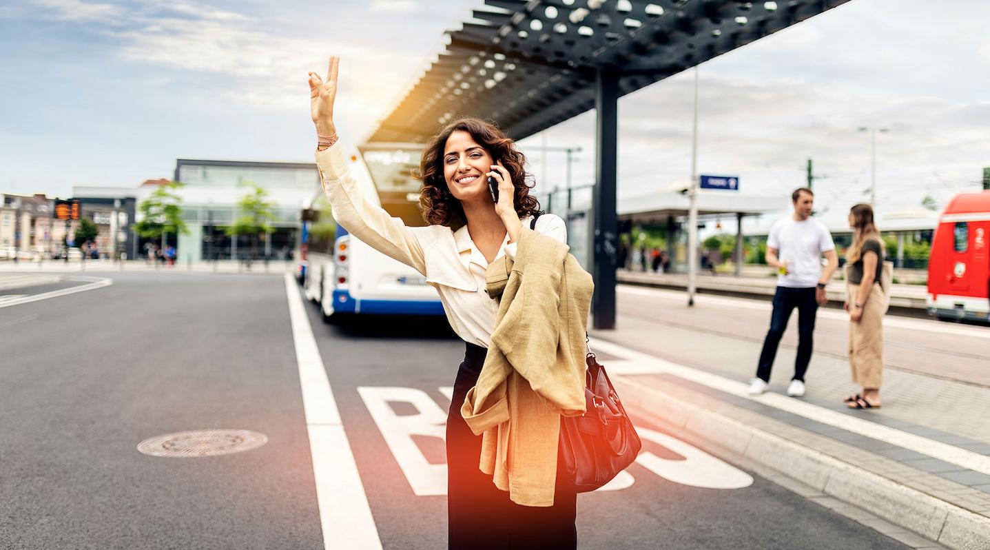 Eine Businessfrau steht an einem Busbahnhof und hält ihre Hand in die Luft, um ein Taxi zu rufen.