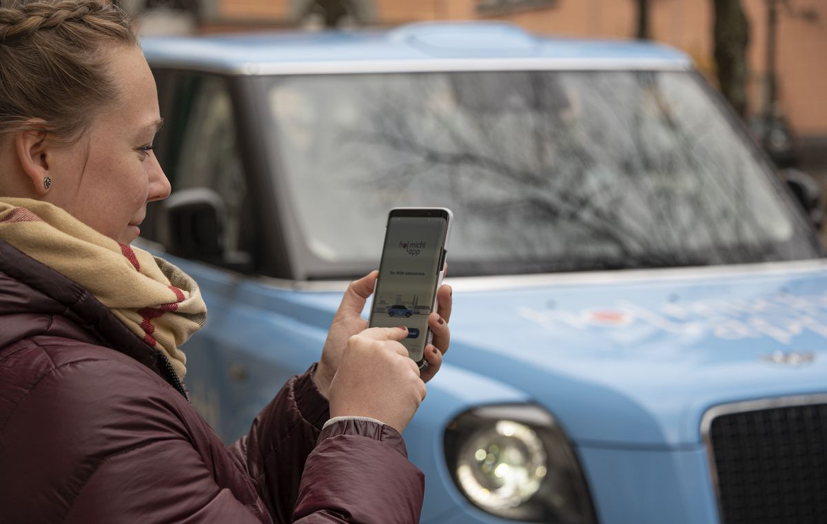 Eine Frau mit einem Smartphone in der Hand steht vor einem kleinen blauen Auto. Auf dem Handybildschirm ist die hol mich! app zu sehen.