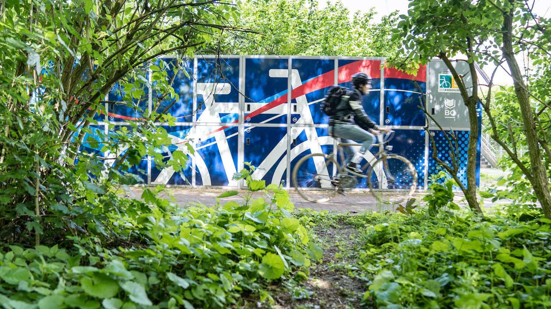 Ein Mann fährt auf einem Fahrrad an einer blauen Radbox vorbei.