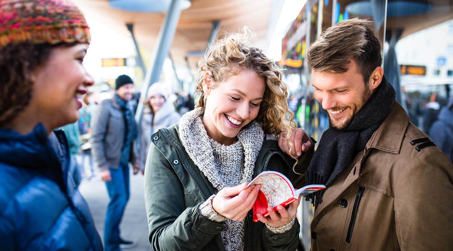 Eine Gruppe von Personen steht lachend an einem Busbahnhof und blättert in einem Ticketflyer.