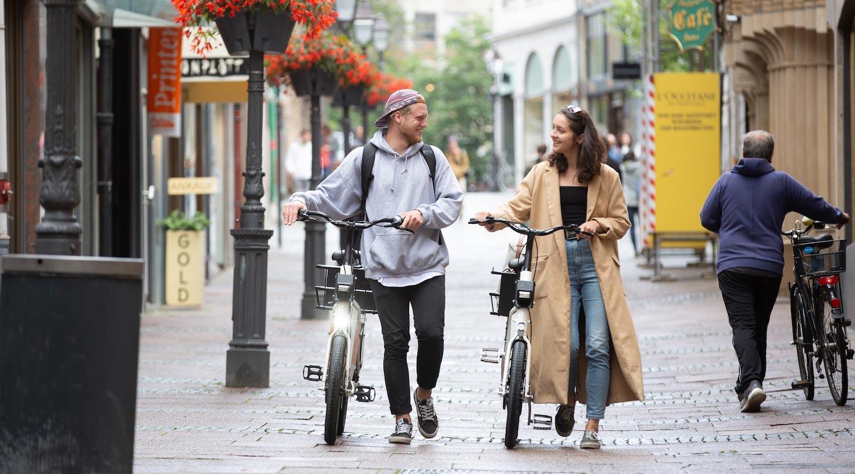 Ein junger Mann und eine junge Frau schieben zwei Fahrräder durch eine Fußgängerzone.
