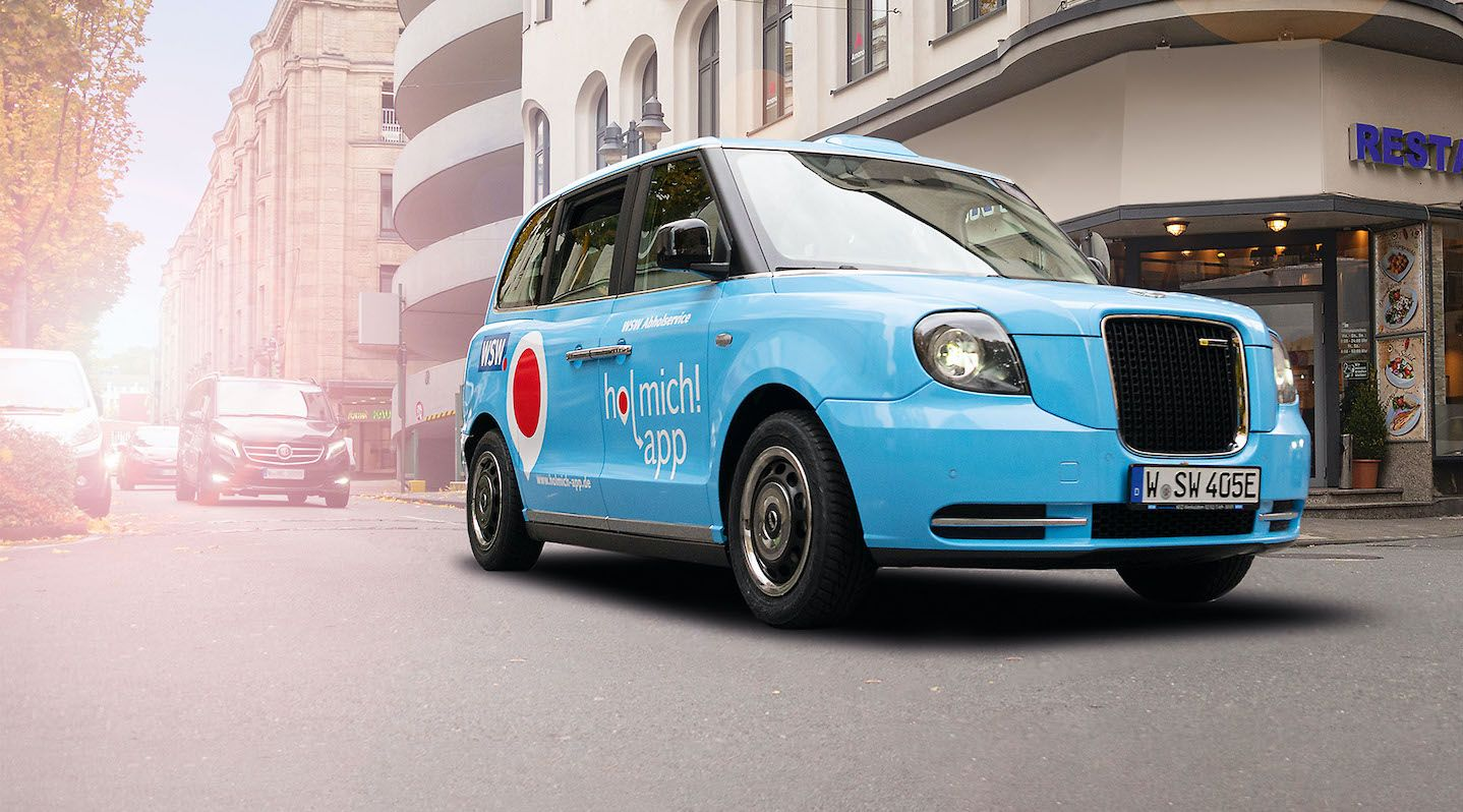 """Ein kleines blaues Auto mit dem Schriftzug """"hol mich! app"""" auf der Seitentür fährt über eine Straße."""
