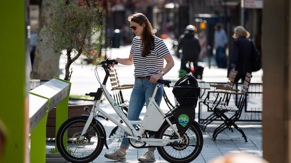 Eine junge Frau schiebt ein E-Bike aus einer Fahrradverleihstation.