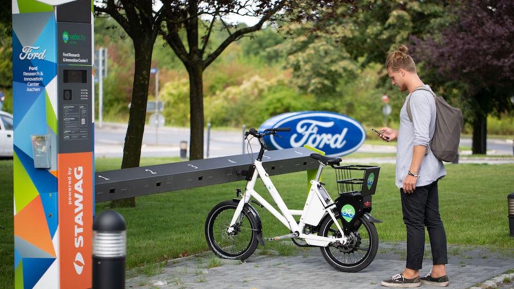 Ein junger Mann steht vor einem E-Bike an einer Verleihstation und schaut auf sein Handy.